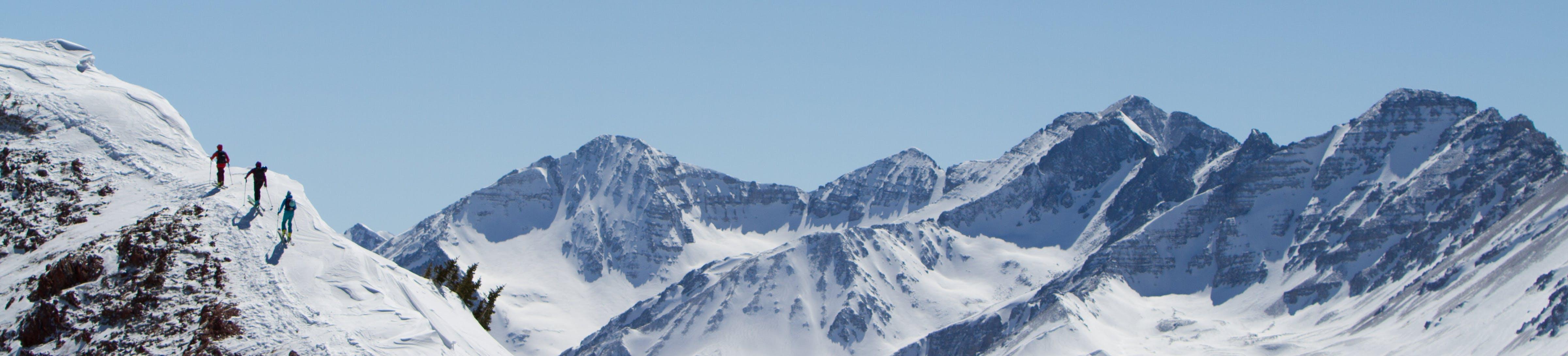 Three skiers traverse a mountain ridge