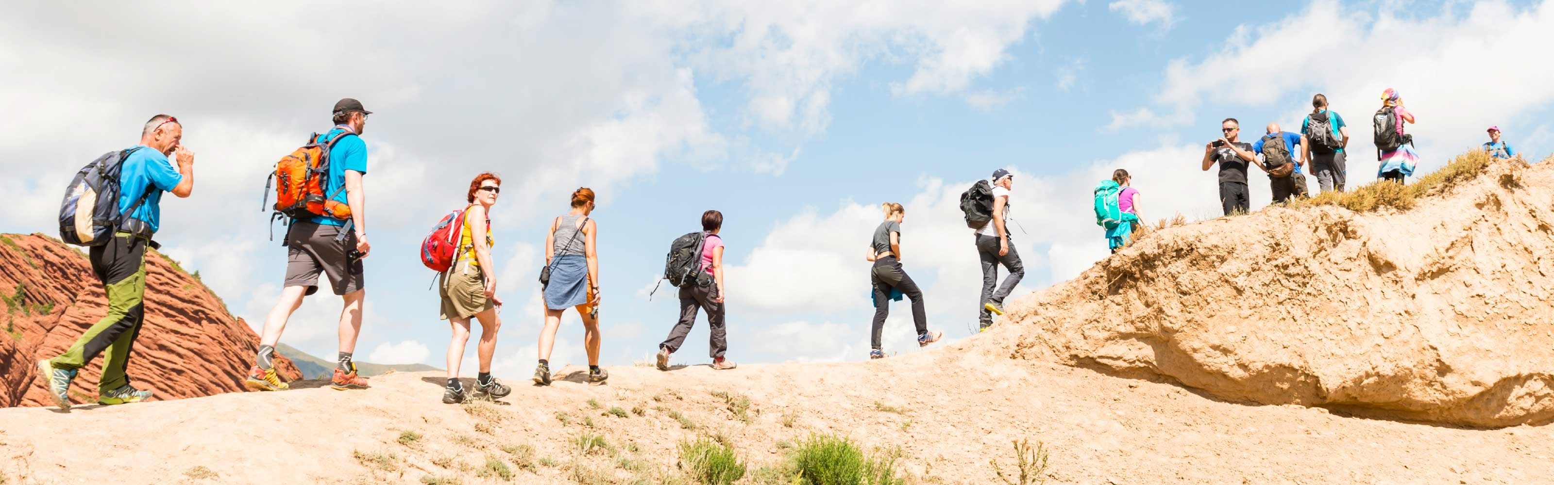 Thirteen hikers wearing backpacks and walking along a ridge